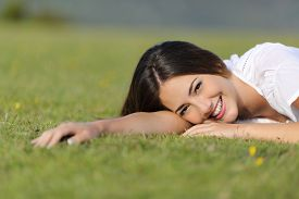 stock photo of sweet dreams  - Happy woman smiling and resting relaxed on the grass in the mountain or a park looking at camera - JPG