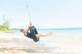 stock photo of tire swing  - Happy woman having fun on tire swing at the beach - JPG
