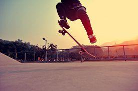 picture of skateboard  - young skateboarder legs skateboarding at outdoor skatepark - JPG