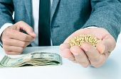 stock photo of buckwheat  - closeup of a young caucasian businessman with a pile of buckwheat seeds in his hand and a pile of dollar banknotes on his office desk - JPG