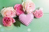 foto of blush  - Blush roses and decorative heart in ray of light on green wooden background - JPG