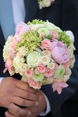 stock photo of chrysanthemum  - Fiance holding beautiful fresh wedding bunch of pink lilac purple white and violet chrysanthemum rose and peony flowers in hand closeup vertical picture - JPG
