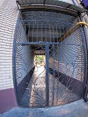 pic of distort  - The entrance to the apartment building closed bars on the background of the setting sun with wide angle fisheye lens and distortion view - JPG
