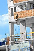 image of formwork  - Crane hoisting formwork over construction site work - JPG