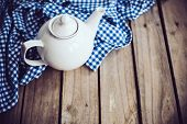 picture of teapot  - Large white porcelain teapot and a blue linen napkin on old wooden board - JPG
