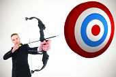 foto of concentration  - Concentrated businessman shooting a bow and arrow against white background with vignette - JPG