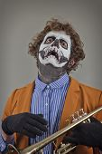 stock photo of clown face  - Crying trumpet player with face painted as human skull - JPG