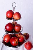 image of serving tray  - Tasty ripe apples on serving tray on brick wall background - JPG
