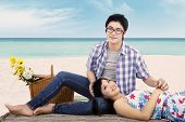 stock photo of couple sitting beach  - Beautiful asian couple relaxing at beach while sitting on mat and smiling at the camera - JPG