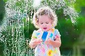 foto of cleaning house  - Little girl washing a window - JPG