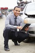 picture of wrecking  - Loss Adjuster Using Digital Tablet In Car Wreck Inspection - JPG