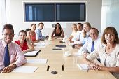 stock photo of pov  - Point Of View Shot Of Businesspeople Around Boardroom Table - JPG
