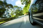 stock photo of speeding car  - SUV speeding on a narrow curve road - JPG