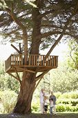 stock photo of grandparent child  - Grandchildren And Grandparents Standing By Tree House In Garden - JPG