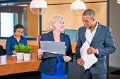 pic of secretary  - Two colleagues meeting in front of a reception desk where a secretary answers calls to discuss project notes - JPG