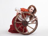 pic of wagon wheel  - young woman with an old wagon wheel on white background - JPG