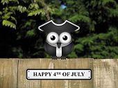 stock photo of bird fence  - Comical bird with happy 4th of July message perched on a timber garden fence against a foliage background - JPG