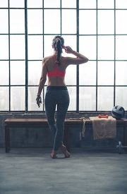 stock photo of crossed legs  - A fit strong muscular woman is standing legs crossed while looking out the window - JPG