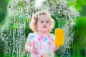 stock photo of detergent  - Little girl washing a window. Kids clean the house. Children help at home. Toddler kid cleaning windows and doors standing on a ladder. Child helping with housework holding sponge and soap bottle. ** Note: Soft Focus at 100%, best at smaller sizes - JPG
