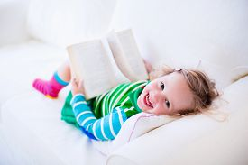 picture of couch  - Little girl reading a book relaxing on a white couch - JPG