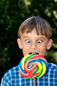 stock photo of buck teeth  - a boy going cross eyed as he looks down at the lollipop that is too big - JPG