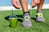 Green smoothie fitness man lacing running shoes, Athlete runner with green vegetable detox juice get poster