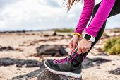 Fitness smartwatch woman runner lacing running shoes on beach, Athlete girl getting ready for run wo poster
