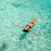 Woman relaxing on blue waves of sea. Happy island lifestyle. Crystal water of tropical beach. Vacati poster