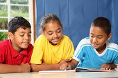 stock photo of girl reading book  - Three happy young primary school friends in class enjoy learning by reading a book together - JPG