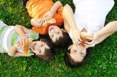 Three children laying on green grass on ground and eating sandwiches and smiling, healthy food, good