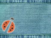 Blue jeans background with ladybug from rags