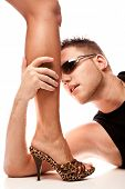 handsome young man holding female leg in high heels, studio white