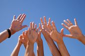 Постер, плакат: многие руки поднятые в голубое небо некоторые motion blur