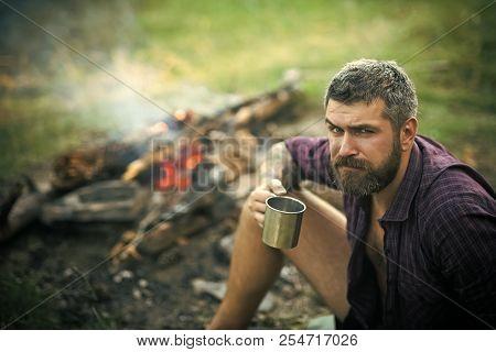 poster of Man Traveler With Mug Relax At Bonfire On Nature. Hipster Hiker Drink Tea At Campfire Flame. Summer