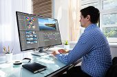 Young Male Editor Editing Video On Computer At Workplace poster