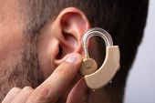 Man Inserting Hearing Aid In His Ear poster