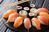 Постер, плакат: Sushi Rolls Set Served On Black Stone Slate On Dark Background