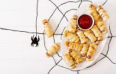 Scary Sausage Mummies In Dough With Funny Eyes On Table. Funny Decoration. Halloween Food. Top View. poster