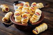 Scary Sausage Mummies In Dough With Funny Eyes On Table. Funny Decoration. Halloween Food. poster