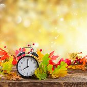 Autumn Time - Fall Leaves With Alarm Clock Over Fall Foliage Background poster