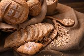 Bread And Rolls In Wicker Basket On Burlap Sack poster