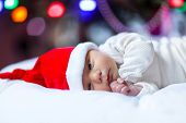 Healthy Newborn Baby In Santa Hat Near Christmas Tree With Colorful Garland Lights On Background. Cl poster