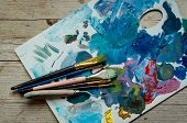 Artist Paint Brushes On Wooden Palette. Texture Mixed Oil Paints In Different Colors. Instruments An poster