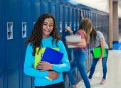 Junior High school Student smiling in a school hallway. Black Female school girl smiling and having  poster