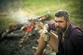 Man Traveler With Mug Relax At Bonfire On Nature. Hipster Hiker Drink Tea At Campfire Flame. Summer  poster