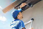 Man Install Outdoor Surveillance Ip Camera For Home Security poster