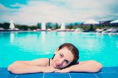 Woman Looks Out Of The Pool, Hanging On The Railing. Young Woman Relaxing In Swimming Pool At Spa Re poster