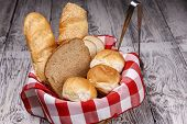 Basket Of Assorted Breads. A Basket Of Assorted Bread Such As Rolls, Sliced Bread, And Baguette. poster