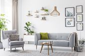 Creative, Wooden Pendant Light Above A Gray Sofa And A Comfy Armchair In A Scandinavian Living Room poster