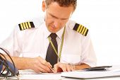 Airline pilot wearing shirt with epaulets and tie filling in and checking papers flight plan, weathe